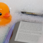 Kindle 3 floating in Trendy Digital case, with rubber duck looking on