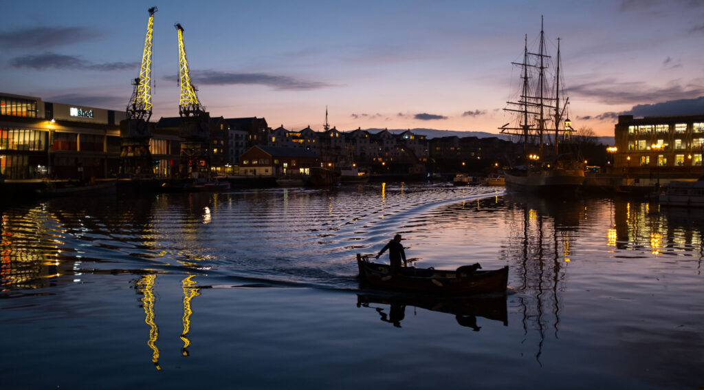 A man and a dog sweep across Bristol harbour in a boat at night