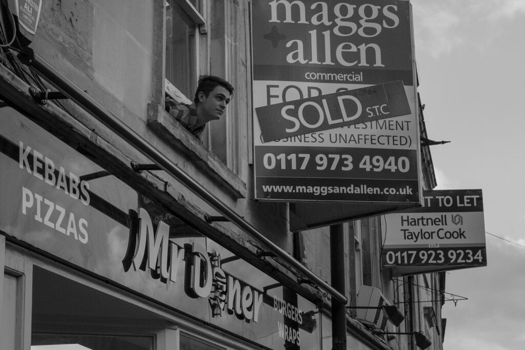 A man pokes his head out of a window on Whiteladies Road