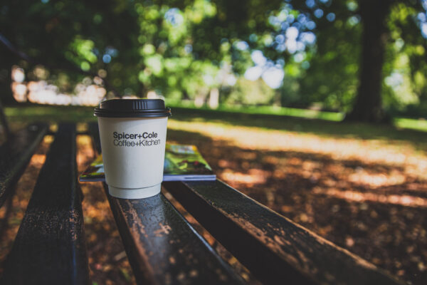 Spicer+Cole take-away coffee cup on a bench in the sunshine