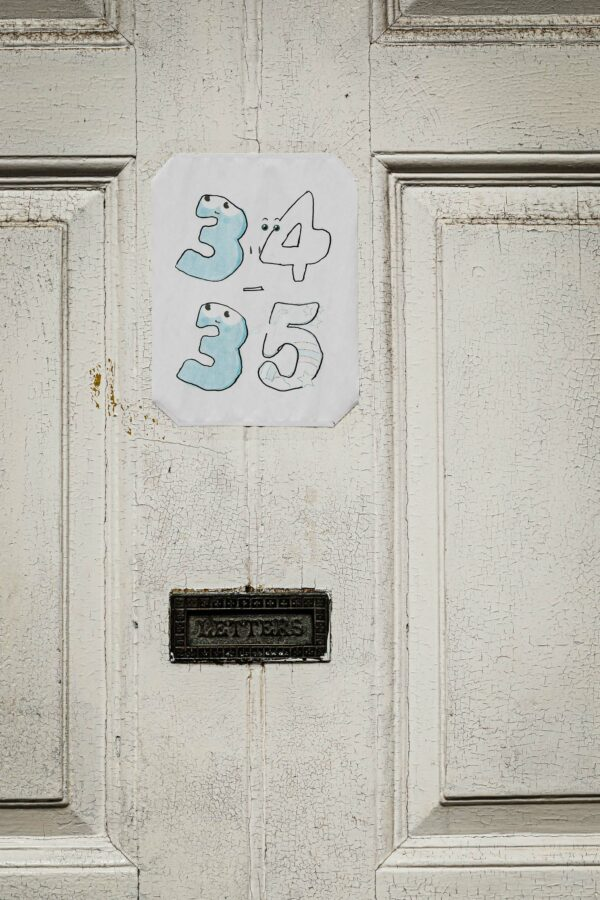 Front door with hand-drawn house numbers and a letter box embossed with LETTERS