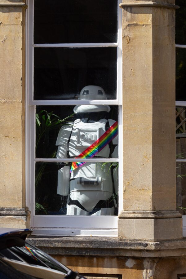 Storm trooper with rainbow bandolier, back turned to viewer, in the window of a Georgian house in Cliftonwood, Bristol