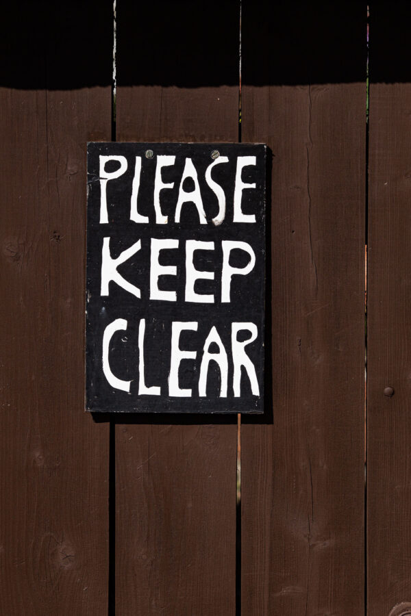 "Hand-lettered sign saying ""PLEASE KEEP CLEAR"""