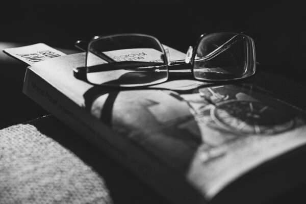 Reading glasses sitting on a copy of Proust's The Way by Swann's