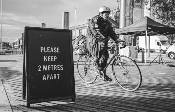 An old man on a bicycle cycles past a PLEASE KEEP 2 METRES APART sign on Bristol's Centre.