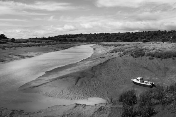 A boat rests on the bank of the River Avon at Sea Mills