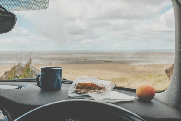 Cheese and pickle sandwich, apple and pannikin of tea on a car dashboard